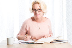 Woman in Glasses Smiles While Reading and Writing At Table Stock Photography