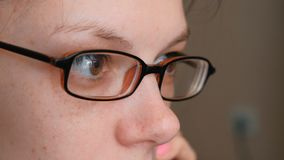 Woman in glasses is speaking mobile phone and looking ahead. Eyes closeup.  stock video footage