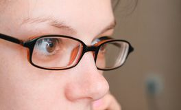 Woman in glasses is speaking mobile phone and looking ahead. Eyes closeup. Woman in glasses is speaking mobile phone and looking ahead. Eyes closeup Royalty Free Stock Photos