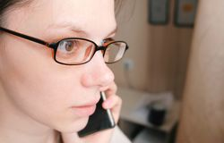 Woman in glasses is speaking mobile phone and looking ahead. Face closeup. Woman in glasses is speaking mobile phone and looking ahead. Face closeup Stock Images