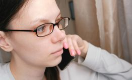Woman in glasses is speaking mobile phone and looking ahead. Side view. Woman in glasses is speaking mobile phone and looking ahead. Side view Royalty Free Stock Photos