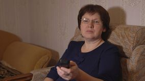 Woman with glasses switches TV channels with a remote control.  stock footage