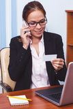 Woman in glasses talking by the phone in the office, business concept Stock Photos