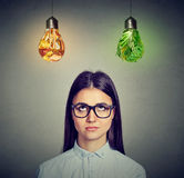 Woman in glasses thinking looking at junk food and green vegetables light bulb Royalty Free Stock Images