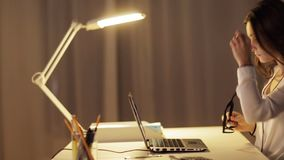 Woman in glasses typing on laptop at night office stock footage