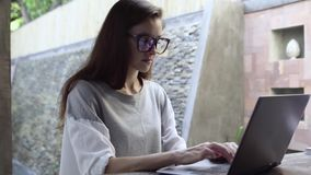 Woman in glasses use laptop. Businesswoman working on computer during vacation. 4K stock video