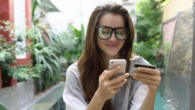 Woman in glasses use online banking on smartphone with credit card near pool in tropical country. stock video footage