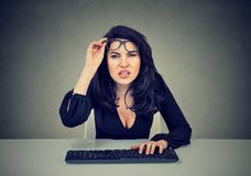 Woman in glasses using computer has vision problems stock photography