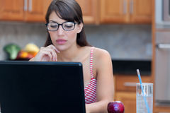 Woman in glasses using laptop computer. Attractive young woman in glasses using laptop computer and possibly working from home, taking online classes, or Royalty Free Stock Photography
