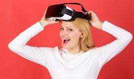 The woman with glasses of virtual reality. Person with virtual reality helmet isolated on red background. Amazed young. Woman touching the air during the VR royalty free stock photography