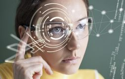 Woman in glasses with virtual screen. Young woman looking at virtual graphics stock image