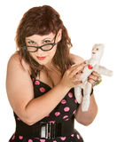 Woman With Glasses and Voodoo Doll Royalty Free Stock Image