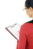 Woman in glasses writing on clipboard Stock Images
