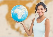Woman with globe against blurry brown map Stock Images