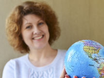 Woman with globe in hands thinking about traveling Royalty Free Stock Photography
