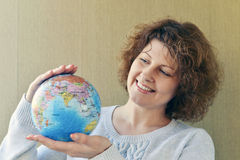 Woman with globe in hands thinking about traveling Stock Image