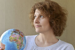 Woman with globe in hands thinking about traveling Stock Photography