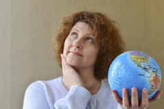 Woman with globe in hands thinking about traveling Royalty Free Stock Photo