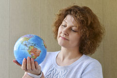 Woman with globe in hands thinking about traveling Royalty Free Stock Image