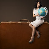 Woman With Globe On Huge Retro Suitcase. Lovely Woman With Globe In Hands Sitting On Huge Retro Suitcase. Space For Text Stock Photo