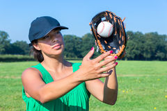 Woman with glove and cap catching baseball Royalty Free Stock Photo