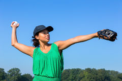 Woman with glove and cap throwing baseball outside Royalty Free Stock Photography