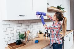 Woman in gloves cleaning cabinet with rag at home kitchen. Stock Photos