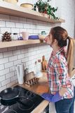 Woman in gloves cleaning furniture with rag at home kitchen. Woman in gloves cleaning furniture with rag at home kitchen Stock Photo