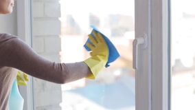Woman in gloves cleaning window with rag stock video footage