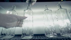 A woman in gloves looks at bottles` quality, using a metal tool. 4K. stock footage
