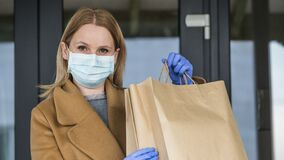 Woman in gloves and mask with bags of groceries on the background of entering the grocery store