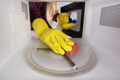 Woman in gloves with sponge and spray bottle cleaning microwave. Stock Photo