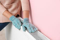 Woman in gloves warming hands on heating radiator. Near color wall. Space for text royalty free stock photos