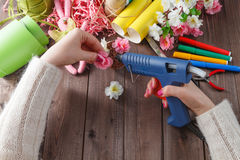 Woman glue handmade flowers with melt gun Royalty Free Stock Images