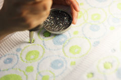Woman glueing sequins to colorful fabrics Stock Photography