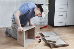 Woman glues together drawer board, assembly of furniture at home Stock Photos