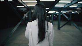 Woman go away at night underground city, rear view. Woman go away at night underground city, back view stock footage