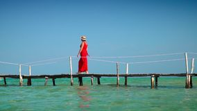 Beautiful woman walking down pier in long red dress. Phu Quoc Island. The woman goes along transparent turquoise water. The woman goes along transparent stock video footage