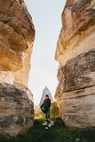 The woman goes between beautiful rocks and admires the landscape in Cappadocia in Turkey Royalty Free Stock Photo