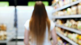 Woman goes into blur through the store with green shopping trolley, between the shelves, supermarket