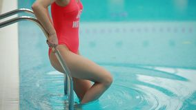 Woman goes down to the pool stock footage