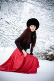 Woman goes on snow. Pretty woman goes on snow and looks at camera Stock Photo