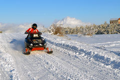 The woman goes on a snowmobile stock photo
