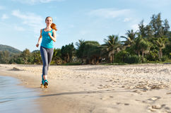 Woman goes in for sports jogging on beach Royalty Free Stock Photography