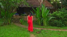 The woman goes to the bungalow on the island. Beautiful Woman in Red Dress Walking in Tropical Garden.  stock video footage