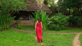 The woman goes to the bungalow on the island. Beautiful Woman in Red Dress Walking in Tropical Garden. Walk in a. On this video you can see as the woman in a red stock footage