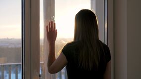 Woman Goes To Window Puts Her Hand On Glass And Looks Out At Street At Sunset
