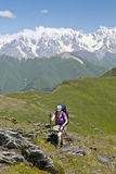 Woman goes uphill with chopsticks. At Caucasus mountains Royalty Free Stock Image