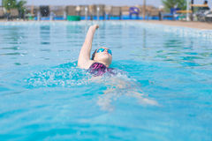 Woman in goggles swimming back crawl style. Young girl in goggles and cap swimming back crawl stroke style in the blue water pool Stock Image
