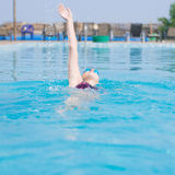 Woman in goggles swimming back crawl style. Young girl in goggles and cap swimming back crawl stroke style in the blue water pool Stock Photos